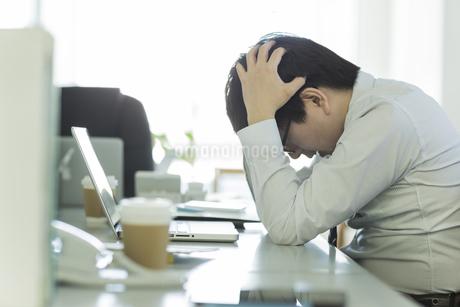 頭を抱えながら嘆くビジネスマンの写真素材 [FYI00042847]