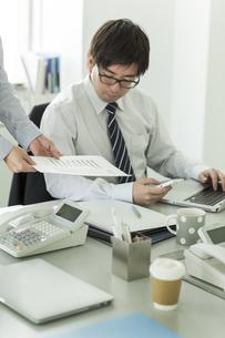 資料を確認するビジネスマンたちの写真素材 [FYI00042850]