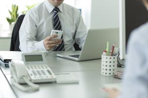 スマートフォンを操作するビジネスマンの写真素材 [FYI00042852]