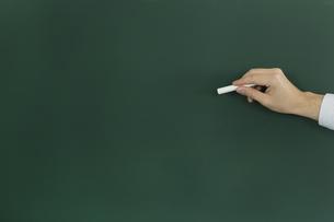 黒板にチョークで何かを書こうとする人の写真素材 [FYI00042859]