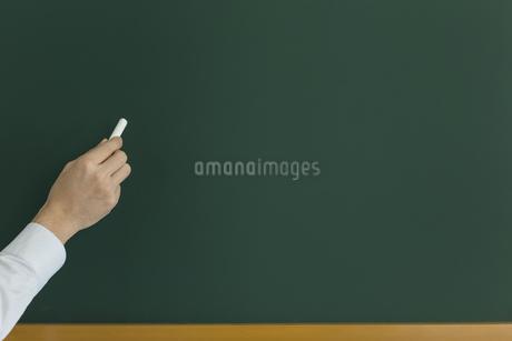 黒板にチョークで何かを書こうとする人の写真素材 [FYI00042866]