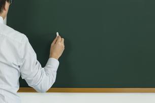 黒板にチョークで何かを書こうとする人の写真素材 [FYI00042867]