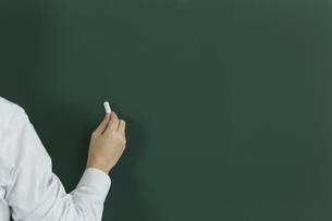 黒板にチョークで何かを書こうとする人の写真素材 [FYI00042869]