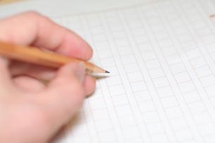 鉛筆を持ち原稿用紙に向かう手の写真素材 [FYI00043451]