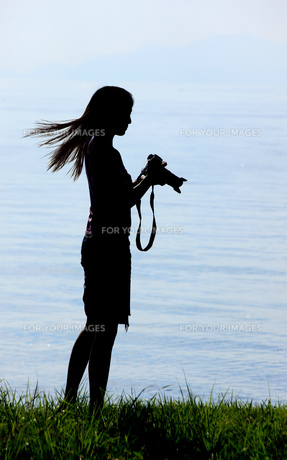 カメラを持った湖畔の女性の写真素材 [FYI00049732]