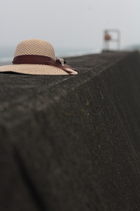 堤防に置かれた麦藁帽子の写真素材 [FYI00057564]