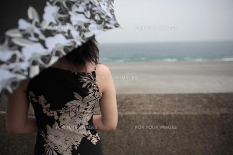 堤防越しに海を見つめる日傘をさした女性の素材 [FYI00057568]