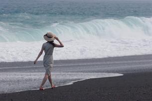 波打ち際を歩く女性の写真素材 [FYI00057576]