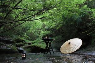 渓流に黒い木のテーブルセットと和傘の写真素材 [FYI00057577]