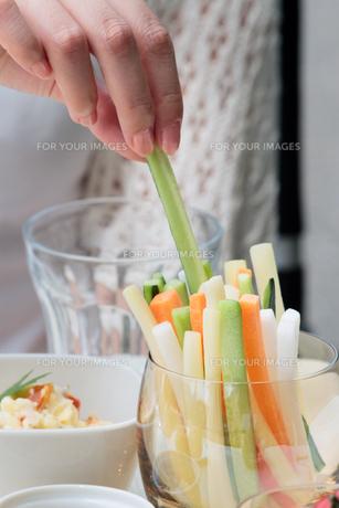 スティックサラダをつまむ女性の手の写真素材 [FYI00057622]