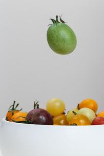 器に盛られたカラフルなトマトの上に浮かぶ緑のトマトの写真素材 [FYI00057643]