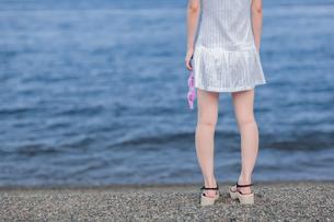 水中眼鏡を持って海岸に佇む女性の写真素材 [FYI00057647]