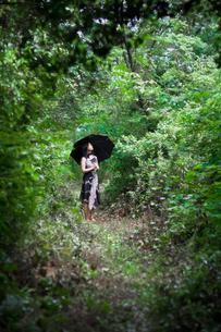 日傘をさして森に立つ女性の写真素材 [FYI00057659]