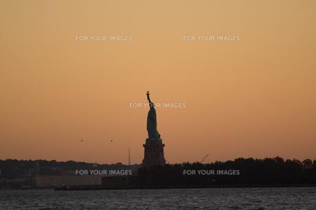 夕焼けに浮かぶ自由の女神の写真素材 [FYI00058659]
