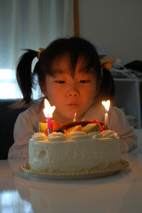 ケーキのロウソクを吹き消す子供の写真素材 [FYI00068279]