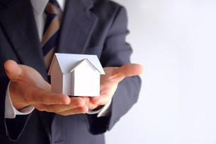 家の模型を差し出すビジネスマンの素材 [FYI00073205]
