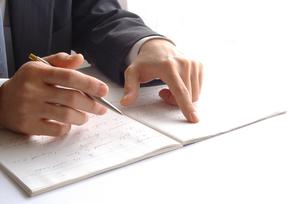 ノートの文字を指差すビジネスマンの写真素材 [FYI00073227]