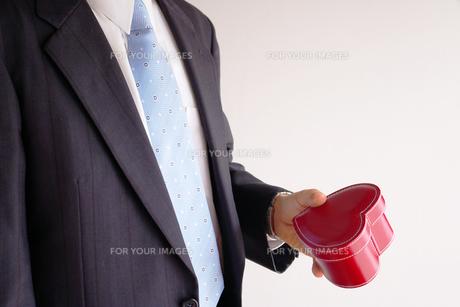 ハートのプレゼントを持つビジネスマンの素材 [FYI00073244]