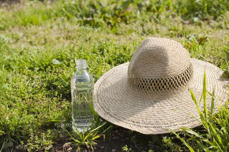 あぜ道のペットボトルと麦わら帽の写真素材 [FYI00080187]
