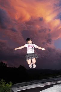 夕焼け雲をバックにジャンプする女の子の写真素材 [FYI00085230]