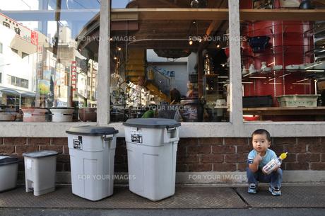 ショーウィンドウの前で座り込む男の子の写真素材 [FYI00086532]