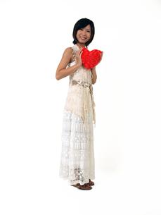 ハートのクッションを両手で持つ女性の写真素材 [FYI00089471]