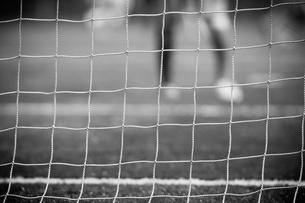 ゴールネット越しのサッカーのゲームの写真素材 [FYI00092165]