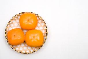 カゴの上の柿の実の写真素材 [FYI00095072]