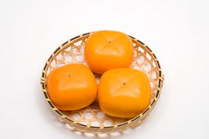 カゴの上の柿の実の写真素材 [FYI00095093]