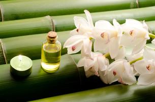 竹の上のエッセンシャルオイルとシンビジウムの花の写真素材 [FYI00096461]