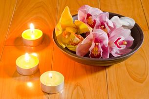 ティーキャンドルと皿の上のシンビジウムの花の写真素材 [FYI00096469]