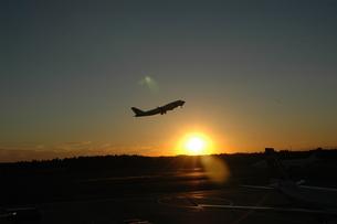 夕暮れに飛び立つ飛行機の写真素材 [FYI00100967]