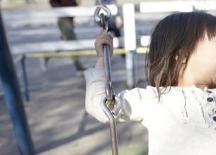 公園でブランコに乗る女の子の写真素材 [FYI00101893]