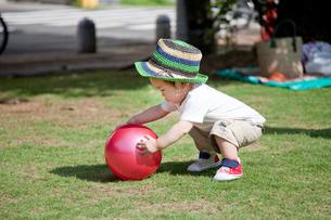 ボールを持ち上げようとする赤ちゃんの写真素材 [FYI00102385]