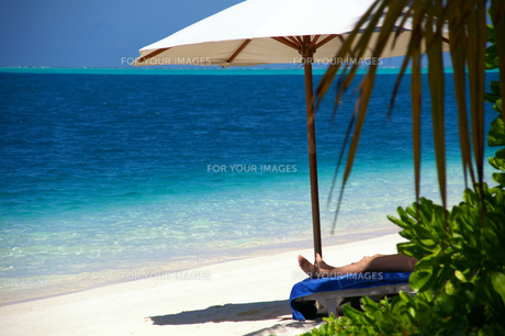 リゾートのビーチで寝そべる人の写真素材 [FYI00103031]