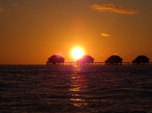 海に沈む夕日と水上コテージの写真素材 [FYI00103039]