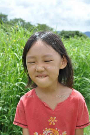 草原を笑顔で歩く女の子の素材 [FYI00106600]