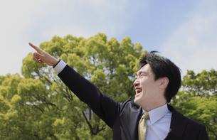 笑顔で空を指差すビジネスマンの写真素材 [FYI00107858]