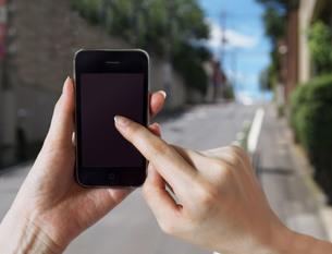 iphoneをクリックする手の写真素材 [FYI00108931]