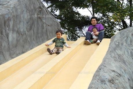 滑り台を滑る親子の写真素材 [FYI00109611]