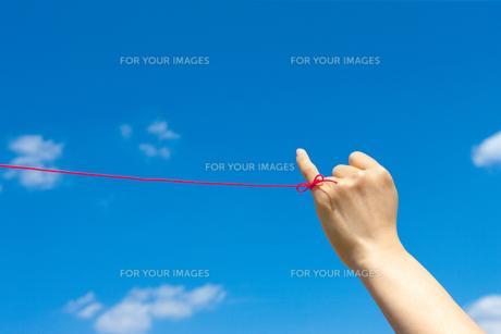 若い女性の左手小指から赤い糸が青い空にの写真素材 [FYI00109994]