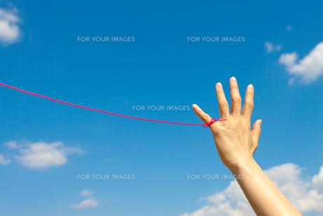 若い女性の左手小指から赤い糸が青い空にの写真素材 [FYI00110002]