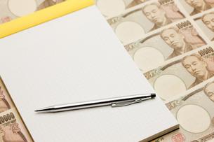 一万円札とノートとペンの写真素材 [FYI00110172]