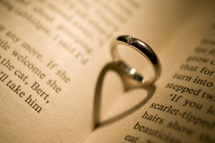 結婚指輪と本に映るハートの写真素材 [FYI00115037]