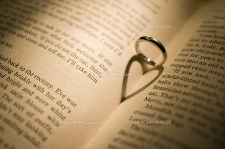 結婚指輪と本に映るハートの写真素材 [FYI00115045]