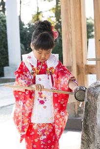 神社でお参りする着物姿の女の子 手水でお清めの写真素材 [FYI00115290]
