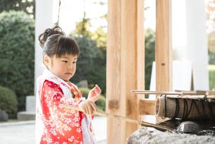神社でお参りする着物姿の女の子 手水でお清めの写真素材 [FYI00115292]