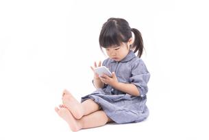 スマートフォンを使う女の子の写真素材 [FYI00115336]