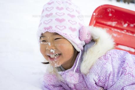 そり遊びで雪が顔にかかった子供の写真素材 [FYI00115339]
