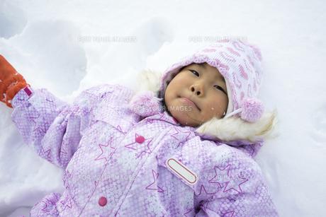 雪の上に寝ころぶ子供の写真素材 [FYI00115371]